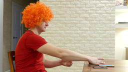 Funny guy in orange afro wig sit by table, cant choose mobile device Footage
