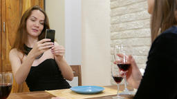 Two pretty girls rest together, drink wine, one take picture using smartphone Footage