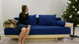 Young woman sit alone at sofa, look aside, speak with someone, Christmas tree Footage