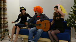 Pranky guy in orange wig sit still with guitar, girl try to kiss, other come in Footage