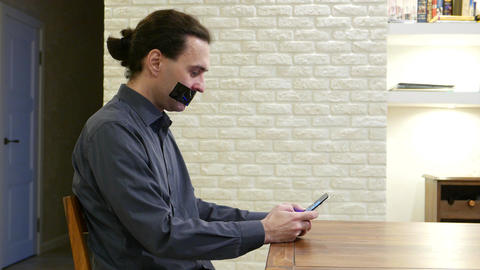 Man sits at table browsing a smartphone, sitting with mouth shut by black tape Footage