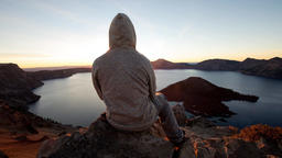 Parallax 2.5D Hooded guy sitting on a rock watching sunrise above crater lake Footage