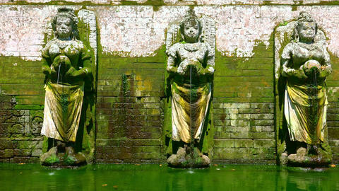 Hindu Goddesses statues making religious offerings. Goa Gajah, Bali. Indonesia Footage