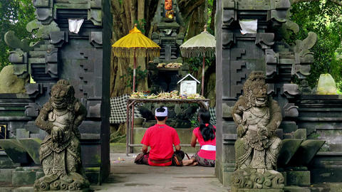 Young couple making offerings and praying at Gunung Kawi Temple. Bali, Indonesia Footage
