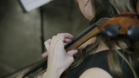 Girl cellist playing cello Close up Footage