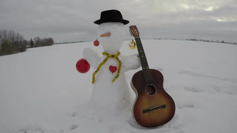 Snowman with retro guitar on field in misty morning, time lapse 4K Footage
