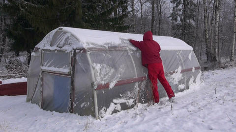 farmer cleaning snow from plastic greenhouse in field Footage