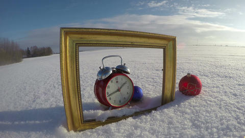 Golden art frame on field snow, Christmas bauble and clock, time lapse 4K Footage