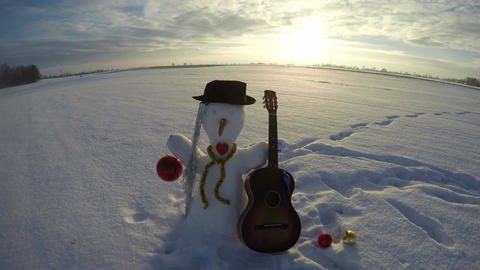 Funny new year snowman on field with guitar, time lapse 4K Footage