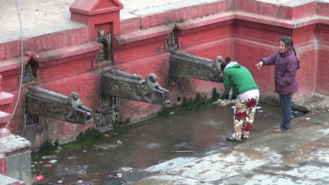 two girls drinking water into container from public fountain. Nepal Footage