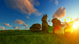 Easter Eggs and Chocolate Bunnies on green meadow against beautiful sunrise Animation