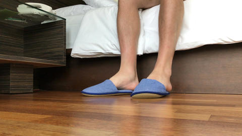 A man dresses slippers in a hotel Filmmaterial
