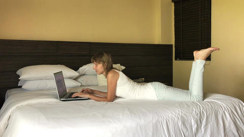 Girl typing on laptop in hotel Footage