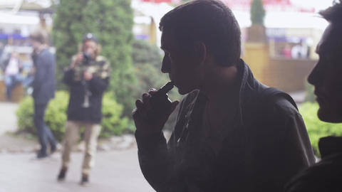 Man exhale steam from electronic cigarette on street. Vapers festival. Smoker Live Action