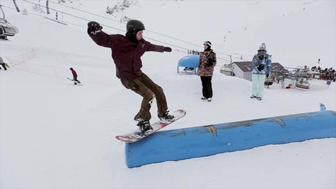 Snowboarder jump on springboard in snowy mountain. Stunts. Contest. Competition. Footage