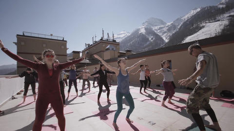 Group of people do yoga at outdoor playground in sunny morning, raise hands. Hea Live Action