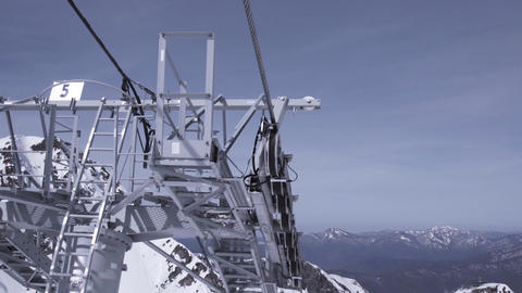 Ski resort. Construction of ski lifts. Height. Sunny day in snowy mountains. Blu Footage