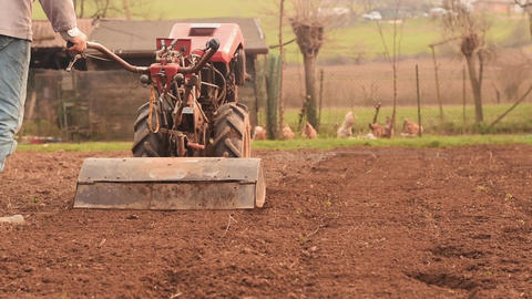 Farmer plowing the field with rototiller Footage