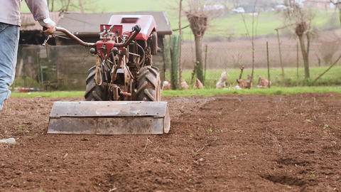 Farmer plowing the field with rototiller. Slow motion Footage