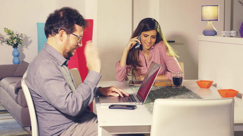 Man and woman working at home with pc and tablet talking on the phone dolly shot Footage