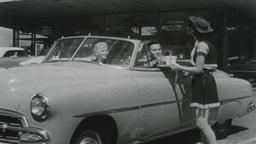 USA 1950s: Cowgirl Carhop Serves Couple Parked in Sedan Footage