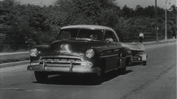USA 1950s: Tracking Auto Pulling Small Boat on Suburb Street Filmmaterial