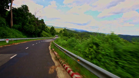 Motion down Country Curvy Road among Hilly Landscape under Sky Footage