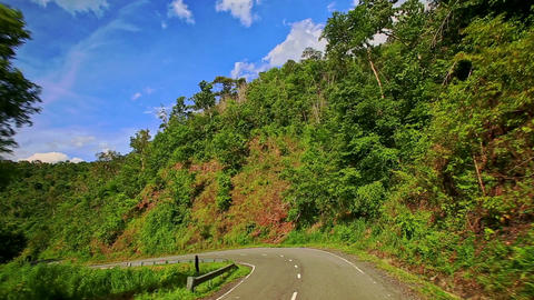 Camera Moves along Curvy Country Road among Hilly Landscape Footage