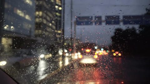 raindrops on windscreen of a moving car with bokeh background at late afternoon  Live Action