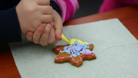 Attentive child decorating star shaped gingerbread with confectionary glaze Footage