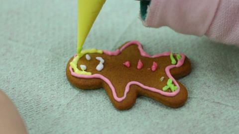 Girl's hands decorating human shaped ginger biscuit, creativity, handmade Footage