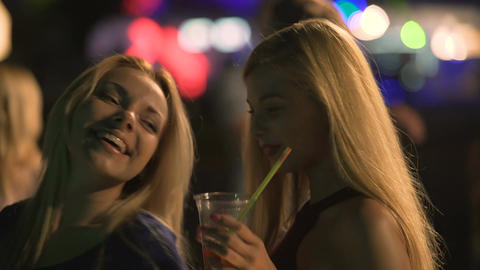 Beautiful blondes flirting on dance floor, making sexy body moves to party music Footage