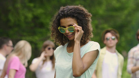 Music festival, beautiful girl wearing sunglasses and flirting with camera Footage