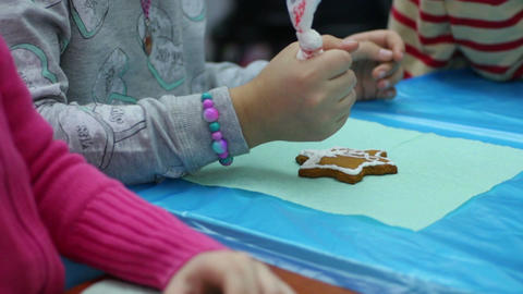 Little girl decorating gingerbread with color glaze, bakery craft, handmade Footage