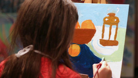 Little girl painting a picture in oil paints, children at art school, hobby Footage