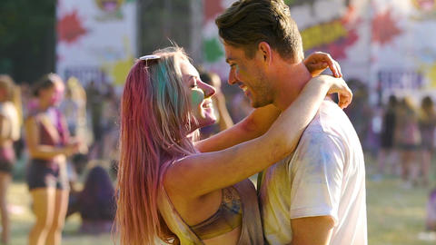 Beautiful couple covered in colored powder hugging and nuzzling at Holi concert Live Action