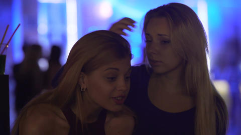 Compassionate young woman supporting upset female friend at nightclub party Footage