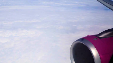 Airliner engine and thick white clouds, view through airplane porthole, tourism Footage