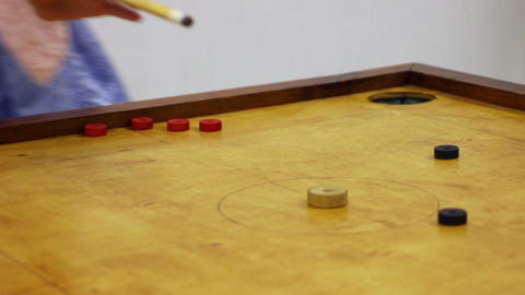 Friends playing carrom table game, girl scoring winning points, leisure time Footage