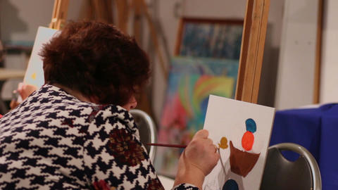 Woman painting a picture in modern arts school, professional painter, hobby Footage