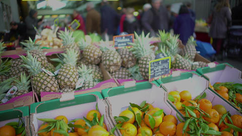 Pineapples and tangerines lying in boxes at food market, exotic fruit trade Footage
