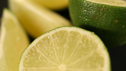 Fresh juicy limes cut in halves turning on stand, preparation of cocktails Footage
