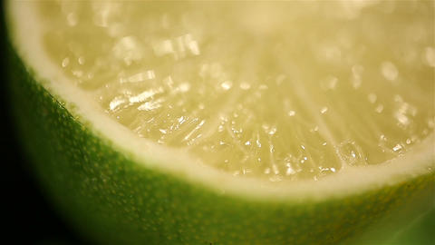 Juicy lime halves rotating on stand, macro. Fresh exotic fruit, healthy eating Footage