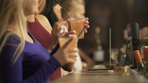 Beautiful young ladies partying, enjoying alcoholic cocktails near bar counter Footage