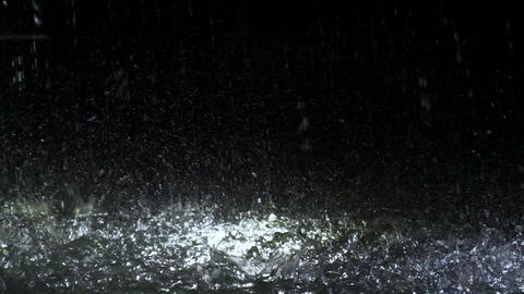 Raindrops falling in fountain at night, fresh waterdrop splashing against ground Footage