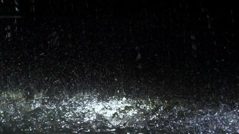 Raindrops falling in fountain at night, fresh waterdrop splashing against ground Footage