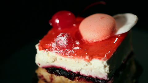 Delicious cake decorated with sweet macaron cookie and cherry, confectionery art Footage