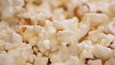 Heap of popcorn in rotation, salty or sweet snack, movie theatre entertainment Footage