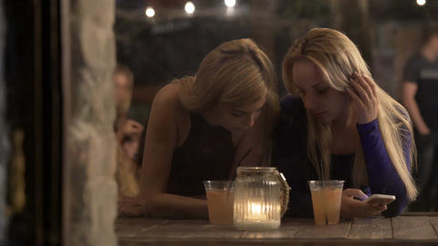 Young women hanging out and having drink at pub, chatting online on smartphones Footage