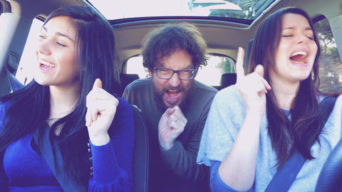 Three happy people in car driving dancing and singing like crazy retro style fun Footage
